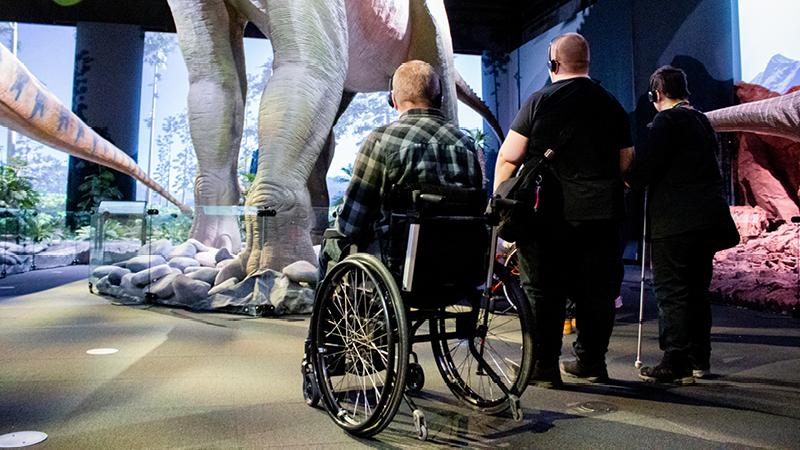 Kuvassa kolme Elä täysii -klubilaista Tiedekeskus Heurekassa katsomassa dinosaurus -näyttelyä klubin esteettömällä retkellä.